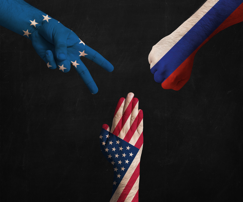 hands decorated in flags of EU, USA and Russia showing Scissors, paper, stone - symbolizing the political games between them